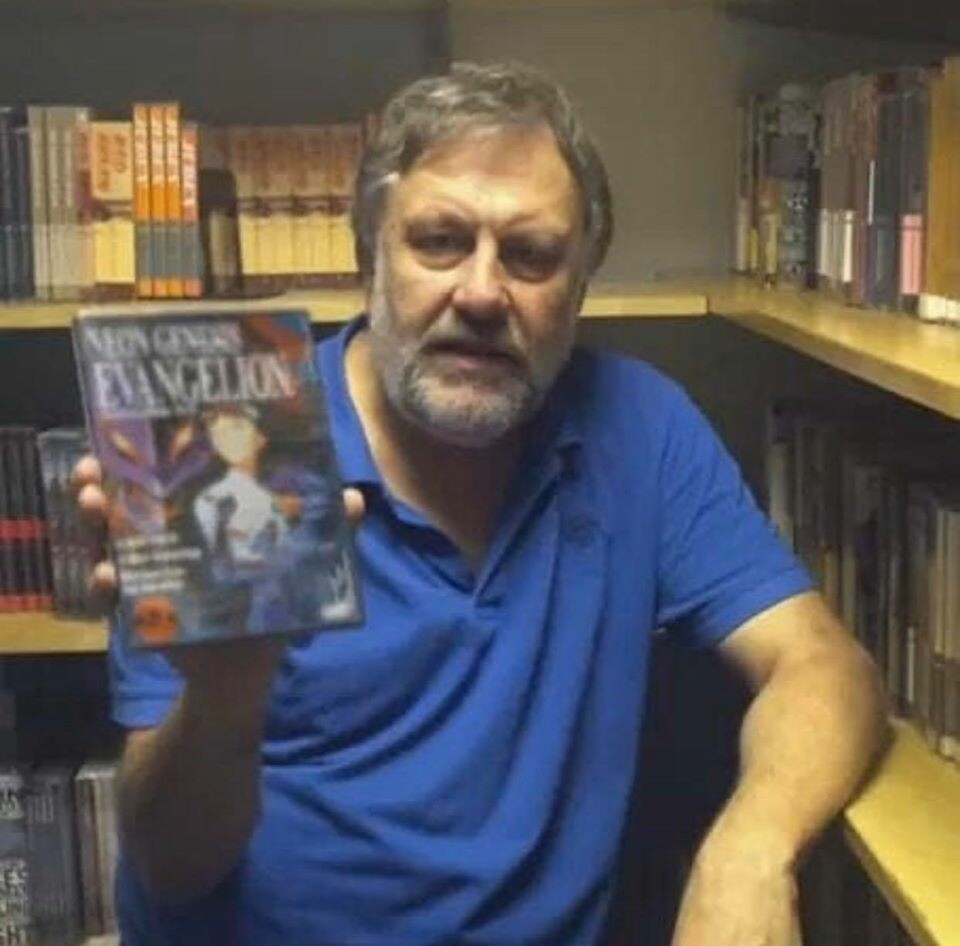 Slavoj Zizek is holding up a dvd case that has the cover of a Neon Genesis Evangelion dvd photoshopped onto it.