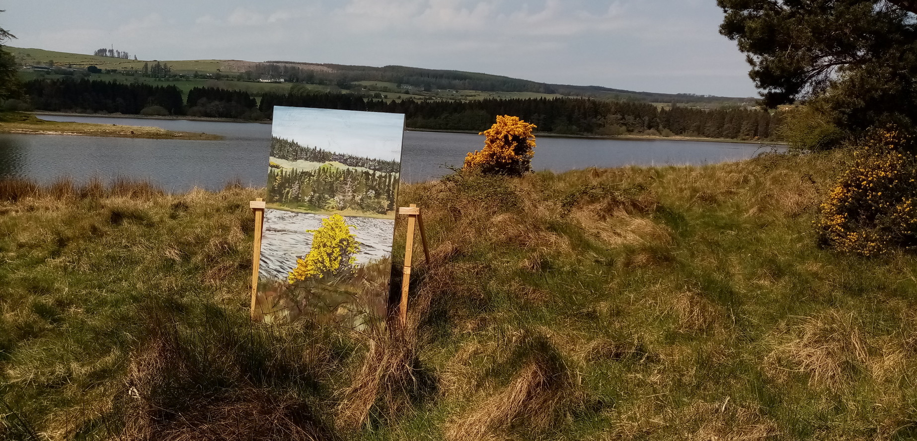 Photograph of a painting made on-site in Wicklow, Ireland, with the painted landscape view in the background
