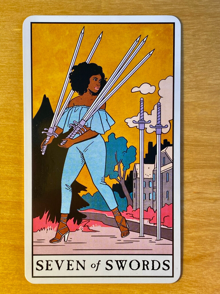 Seven of Swords from the Modern Witch Tarot: a Black woman in tight blue pants and a sun top steals away from a mansion with her hands full of swords